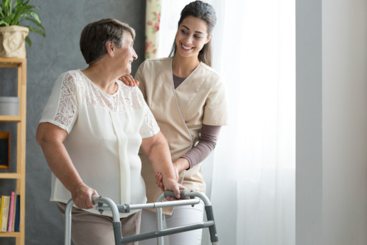a nurse is helping an old woman to walk