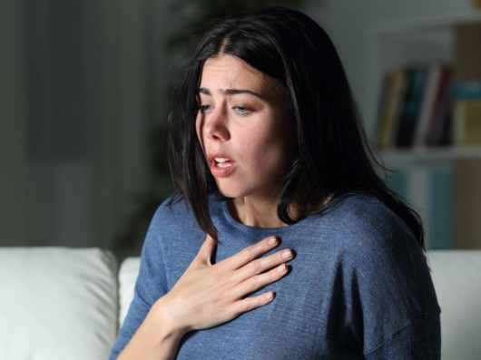 A worried girl holding her hand on the chest showing her anxiety