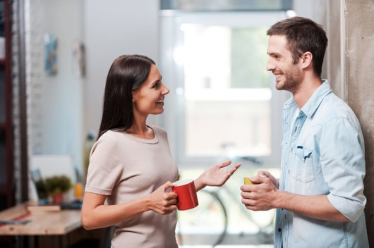 A girl with a red cup is talking happily to a guy