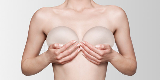 A close up torso of the girl who is covering her breast with breast implants