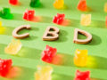 CBD on a green background and gelatin in the form of bears.
