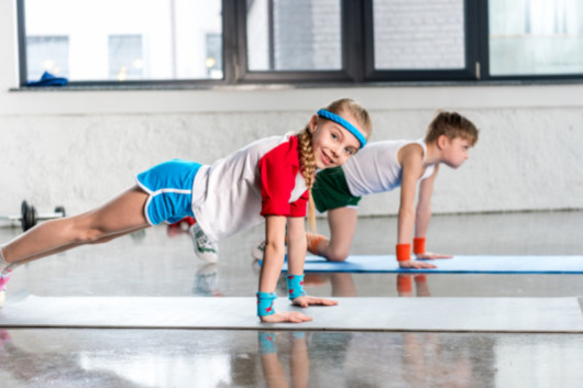 A young boy and a girl in a fitness outfit are standing in a plank