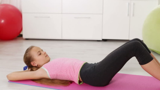 Young girl is exercising at home on a pinky mat