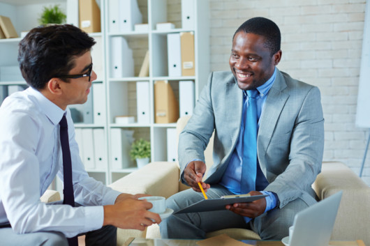 Healthcare Insurance Administrator is taking to the guy and showing him something