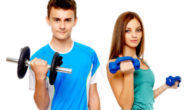 Teenage girl and a boy on the white background holding dumbbells