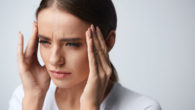 Girl is keeping her fingers at the temples due to a severe headache