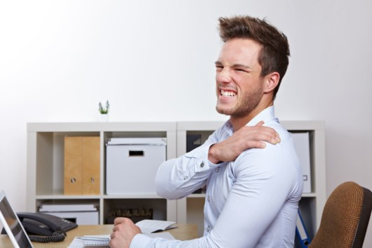 Guy writhing with pain holding his shoulder