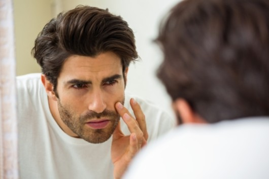 Young man is checking his face for wrinkles or age changes in front of the mirror