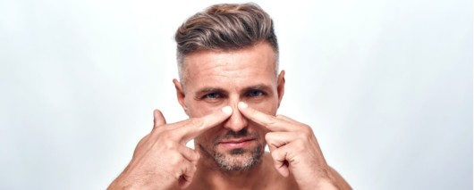close up face of a guy on white who keeping his fingers at his nose to show he need the rhinoplasty
