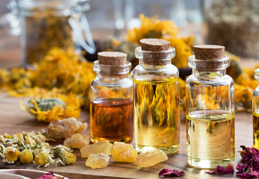 Three transparent bottles filled with essential oils are on the table with dry yellow flowers and natural pieces of salt around