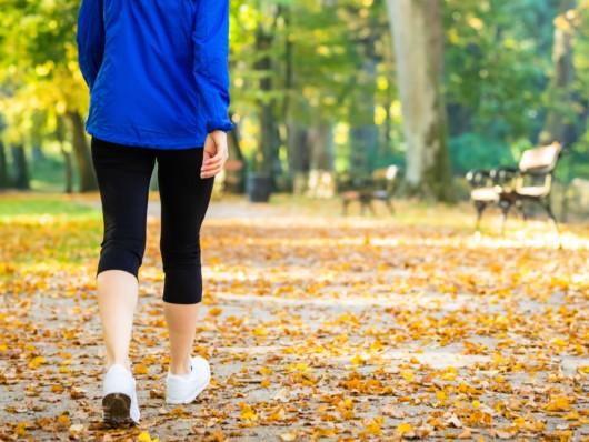 Girl in blue jacket is walking in the park in autumn