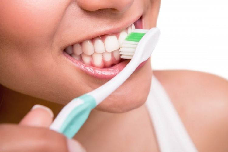 Close up picture of the girl who is brushing her teeth