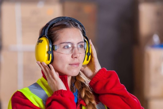 A young lady is wearing yellow headphones to protect her ear from loud noise at work