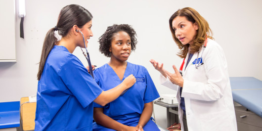 A doctor is teaching a young medical assistant how to treat a patient