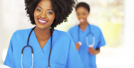 A black woman dressed as a medical assistant in blue outfit is smiling into the camera