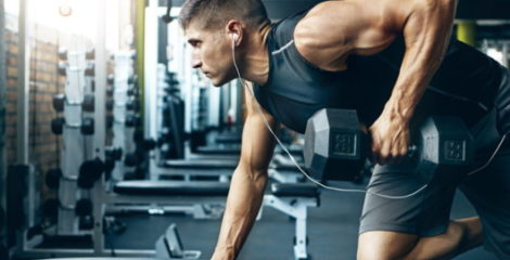 A strong and physically developed guy is exercising in the gym with a dumbbell