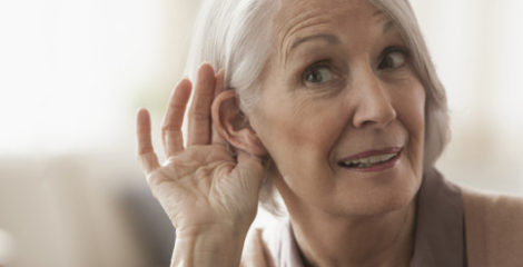 An elderly woman is trying to listen with cupping her ear