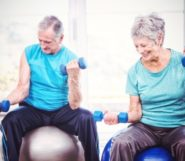 Senior people are doing exercises on the fitness balls with dumbbells