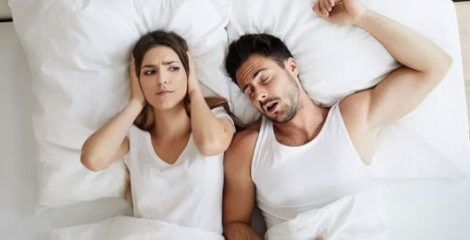 A couple is lying on the bed. Guy is snoring and the girl covered her ears